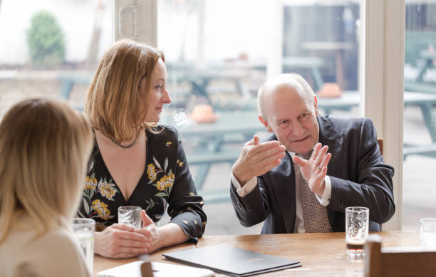 Professional real people, young adult woman, senior man, having informal business meeting in pub stock photo