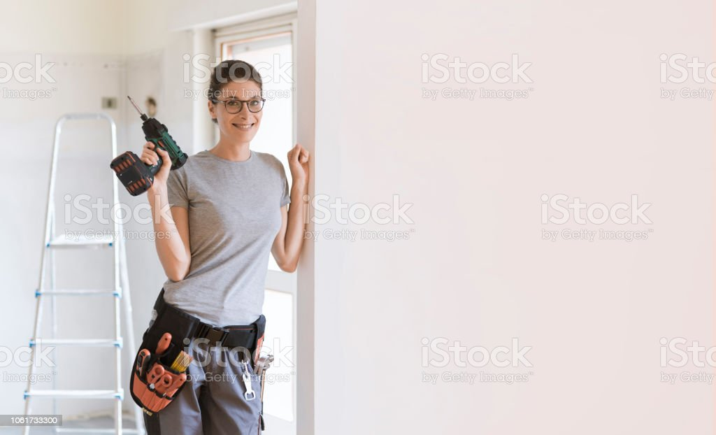 Professional repairwoman posing and holding a drill stock photo
