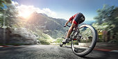 An athlete is riding a bicycle on a spiral track high in the mountains.  The man is wearing black bike shorts and shin guards along with a red sleeveless top and a red and white helmet and sunglasses. The image is blurred in motion.