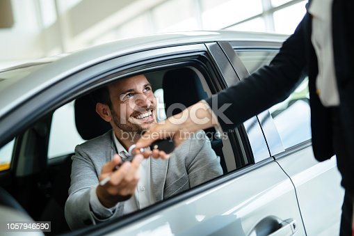 Professional woman salesperson during work with customer at car dealership.