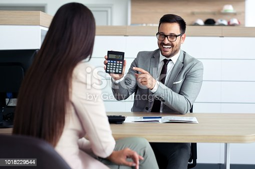 988321834 istock photo Professional salesperson selling cars at dealership to buyer 1018229544
