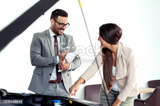 988321834 istock photo Professional salesperson selling cars at dealership to buyer 1020448544