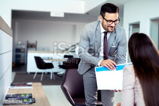 988321834 istock photo Professional salesperson selling cars at dealership to buyer 1028050234