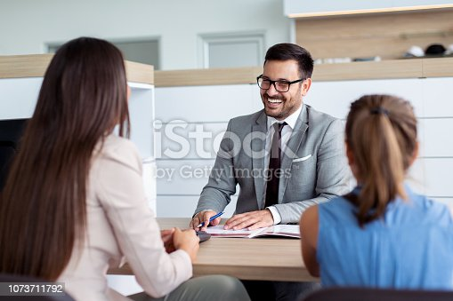 988321834 istock photo Professional salesperson selling cars at dealership to buyer 1073711792