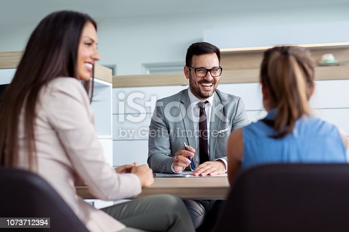 988321834 istock photo Professional salesperson selling cars at dealership to buyer 1073712394