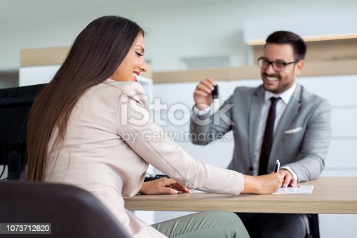 988321834 istock photo Professional salesperson selling cars at dealership to buyer 1073712620