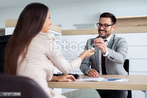 988321834 istock photo Professional salesperson selling cars at dealership to buyer 1073712836