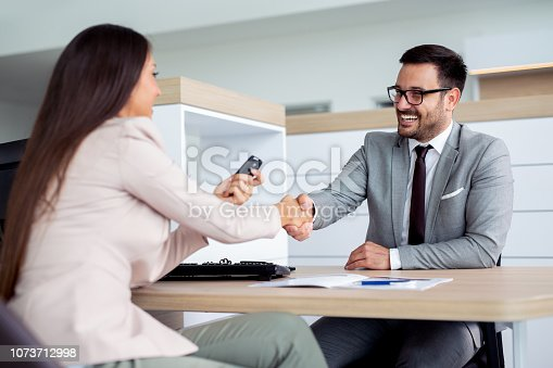 988321834 istock photo Professional salesperson selling cars at dealership to buyer 1073712998