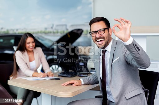 988321834 istock photo Professional salesperson selling cars at dealership to buyer 1073714838