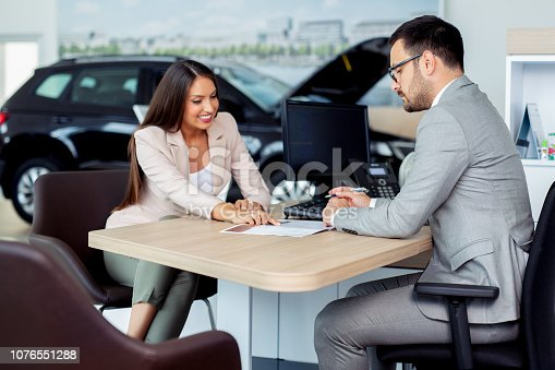 988321834 istock photo Professional salesperson selling cars at dealership to buyer 1076551288