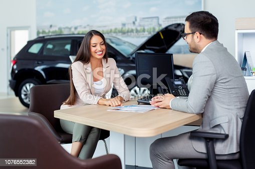 988321834 istock photo Professional salesperson selling cars at dealership to buyer 1076552382