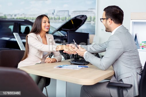 988321834 istock photo Professional salesperson selling cars at dealership to buyer 1076553460