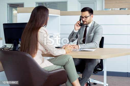 988321834 istock photo Professional salesperson selling cars at dealership to buyer 1076558802