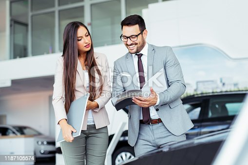 988321834 istock photo Professional salesperson selling cars at dealership to buyer 1187105574