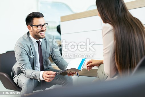 988321834 istock photo Professional salesperson selling cars at dealership to buyer 1187105619