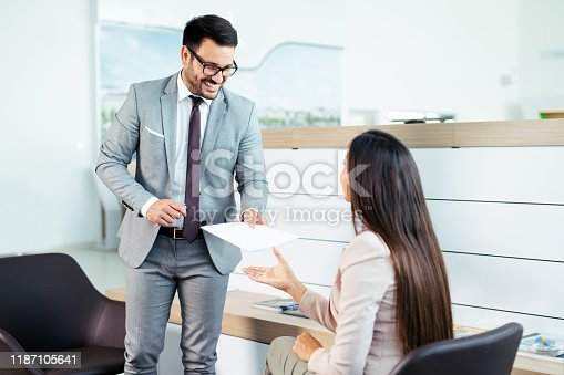 988321834 istock photo Professional salesperson selling cars at dealership to buyer 1187105641