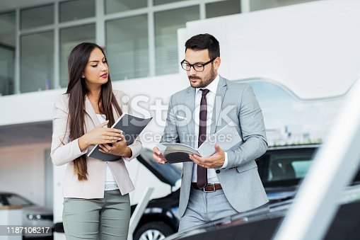 988321834 istock photo Professional salesperson selling cars at dealership to buyer 1187106217