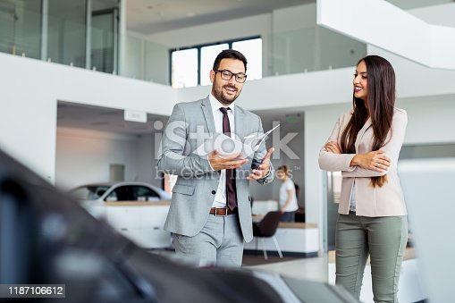 988321834 istock photo Professional salesperson selling cars at dealership to buyer 1187106612