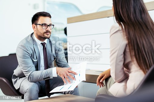 988321834 istock photo Professional salesperson selling cars at dealership to buyer 1187106783