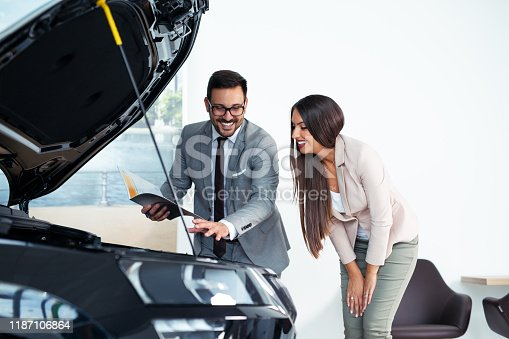 988321834 istock photo Professional salesperson selling cars at dealership to buyer 1187106864