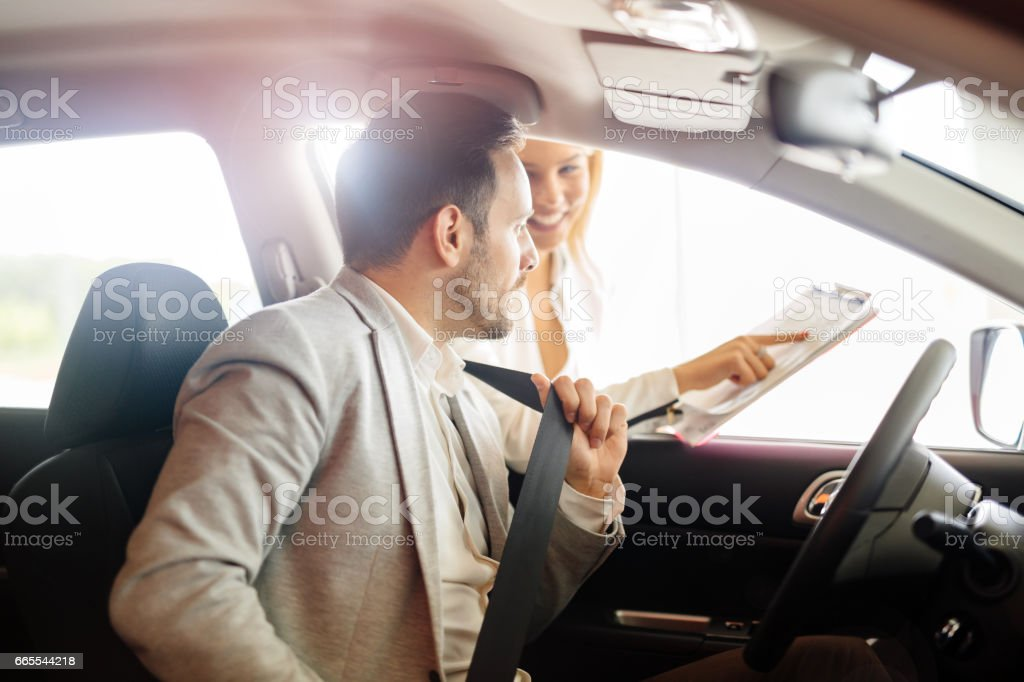 Professional salesperson selling cars at dealership to buyer stock photo