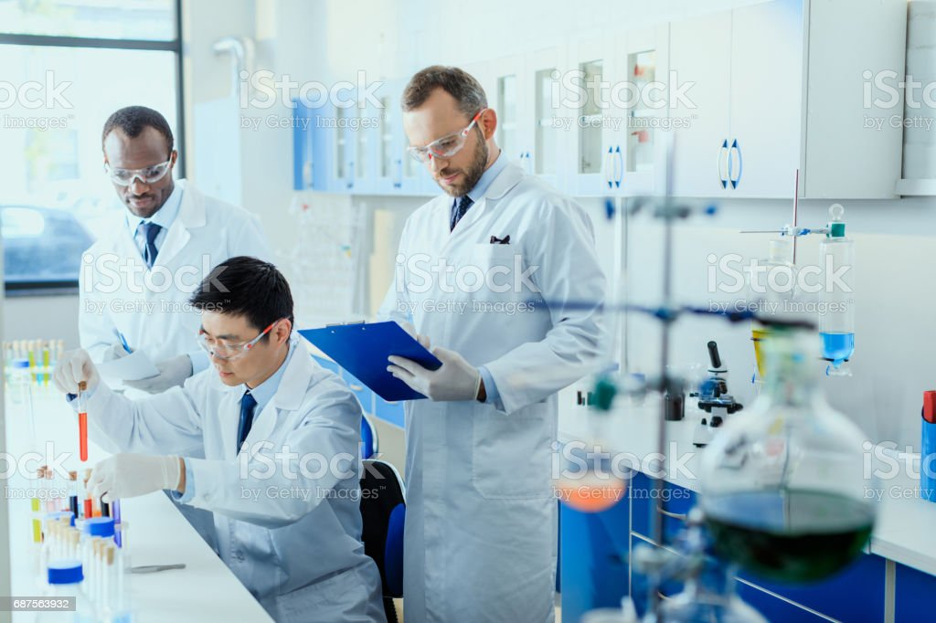 Professional scientists in white coats working together in chemical laboratory stock photo