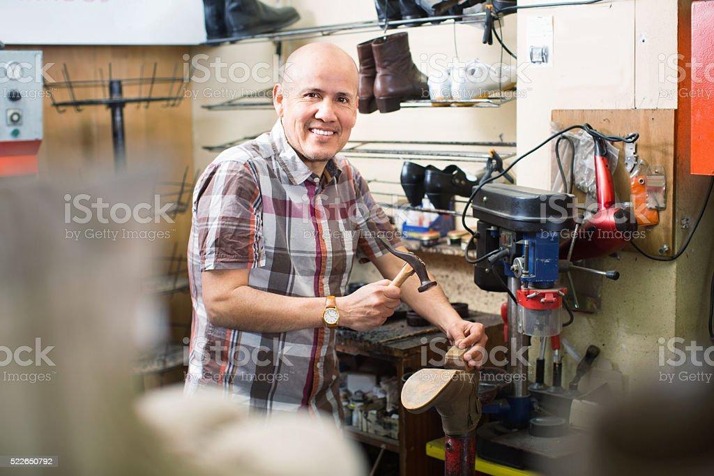Professional  shoemaker heeling footwear on machine stock photo