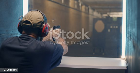 Back view of middle aged man shooting rifle fast then pushing button and waiting for target to move closer in range