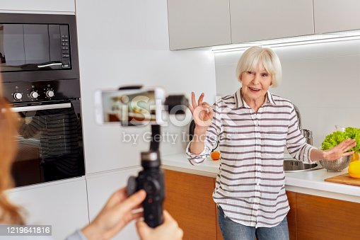 1179265329 istock photo Professional shooting team record video interview for public blog vlog. Fashion modern style grandmother old woman seniordemonstrating detox healthy fresh easy recipe. CopySpace horizontal like share 1219641816