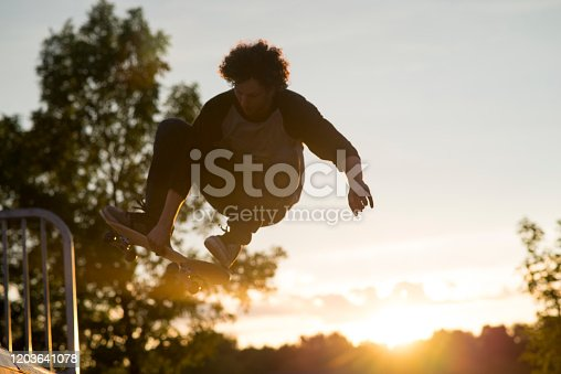 Semi silhouette of a young man with curly hair wearing casual clothing in the air during a skateboard trick off of a ramp at the skateboard park at sunset during the summer time.