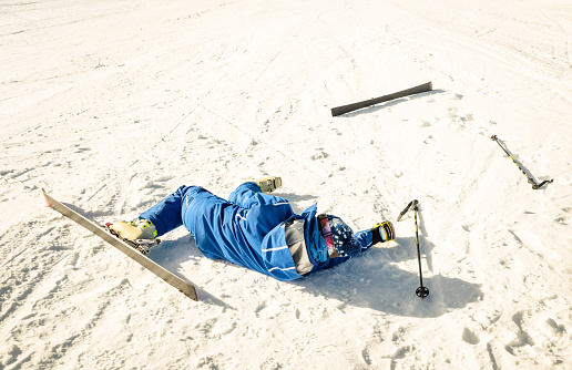 Professional skier after crash accident on skiing resort slope - Winter sport emergency concept with athlete needing help assistance on dramatic trouble situation - Warm sunny afternoon color tones
