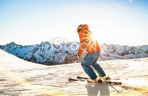 Professional skier athlete skiing at sunset on top of french alps ski resort - Winter vacation and sport concept with adventure guy on mountain top riding down the slope - Warm bright sunshine filter