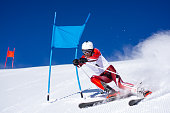 aggressive ski turn man male skier during super g race close to goal on piste sunny winter day clear blue sky