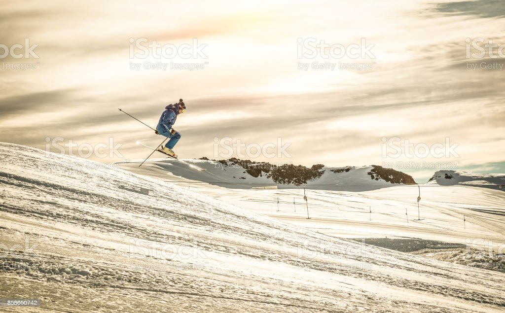 Professional skier performing acrobatic jump on downhill exhibition - Extreme winter sport concept with skiing athlete competing at international race - Dramatic contrasted filter with sunshine halo stock photo
