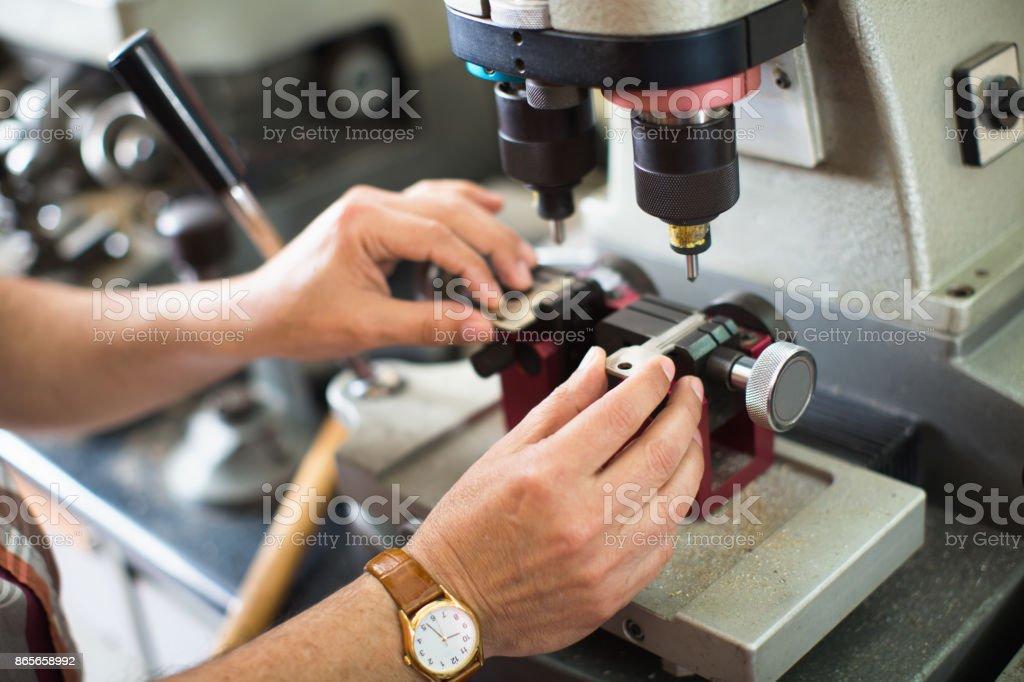 Profissional qualificado cortador chave, fazendo porta chaves cópias foto de stock royalty-free