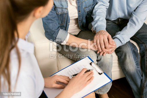 Couple therapy. Professional smart female psychologist holding her notes and talking to a married couple while having a psychological session with them