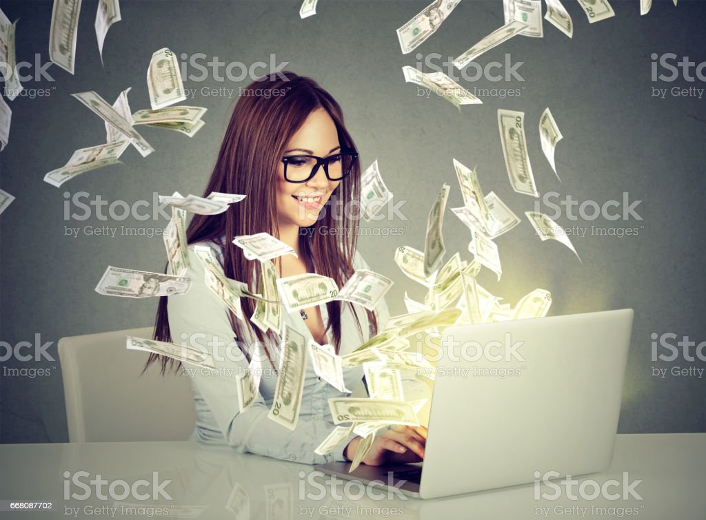Professional smart young woman using a laptop building online business Professional smart young woman using a laptop building online business making money dollar bills cash coming out of computer. Beginner IT entrepreneur success economy concept Adult Stock Photo