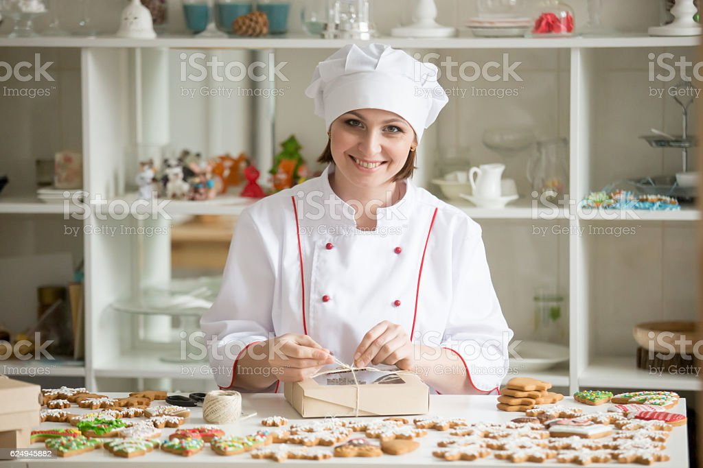 Professional smiling confectioner wrapping a box with cookies stock photo