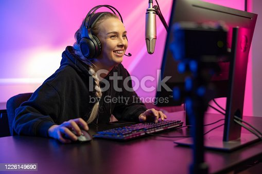 Smiling and excited professional blonde esport gamer woman with headphones streaming vlog live while playing online video game on her PC. Room with blue and pink colored LED lights.