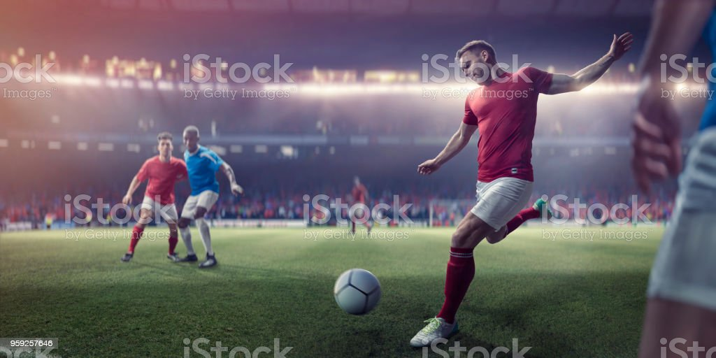 A professional male soccer player with foot back and arms out about...