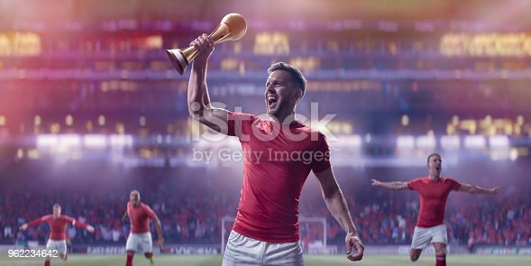 istock Professional Soccer Player Holding Up Gold Trophy In Victory Celebration 962234642