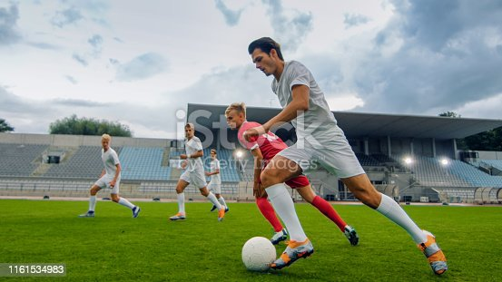 istock Professional Soccer Player Leads with a Ball, Masterfully Dribbling and Bypassing Sliding Tackles of His Opponents. Two Professional Football Teams Playing. Low Angle Shot. 1161534983