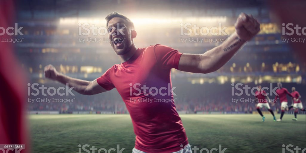 Professional Soccer Player With Arms Out Shouts in Victorious Celebration stock photo
