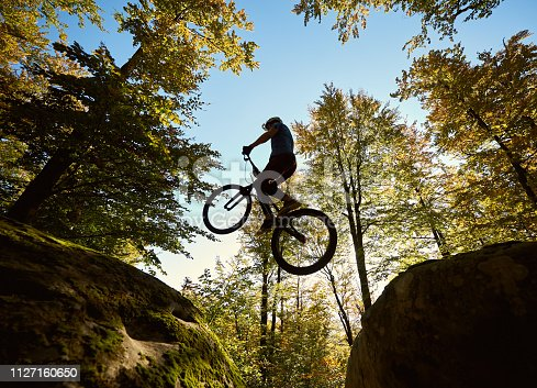 Young male biker jumping on trial bicycle between two big boulders, professional rider making acrobatic trick in the forest on sunny day. Concept of extreme sport active lifestyle