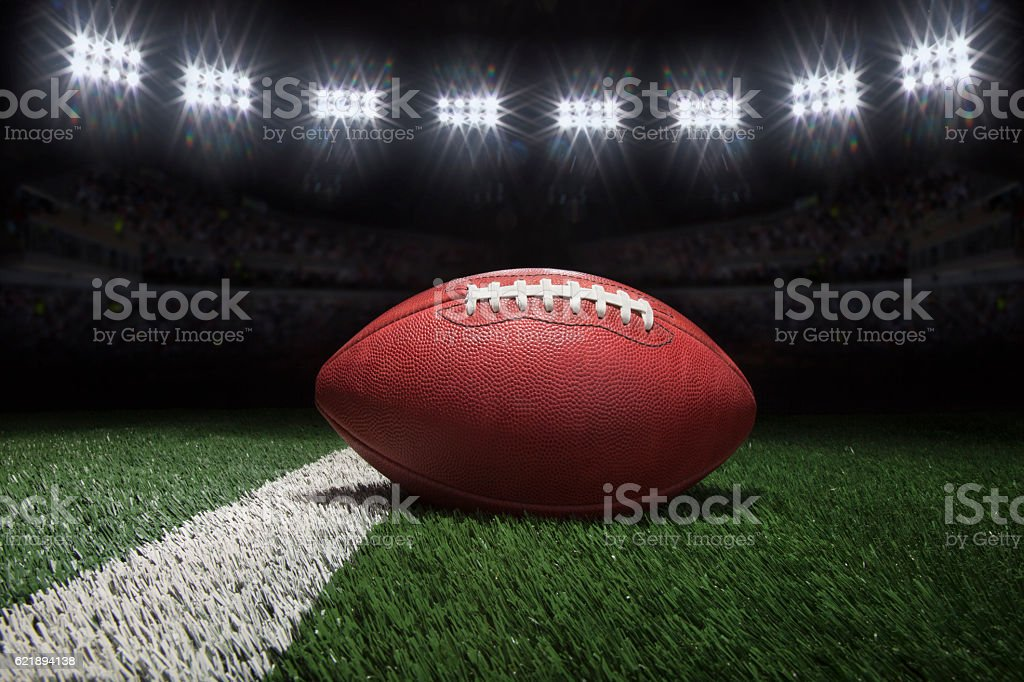 Professional style football on field with stripe under stadium lights stock photo