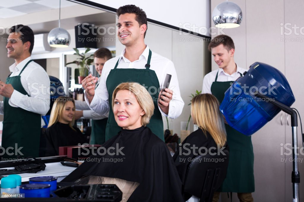 Professional stylist cutting hair of elderly blonde - foto stock