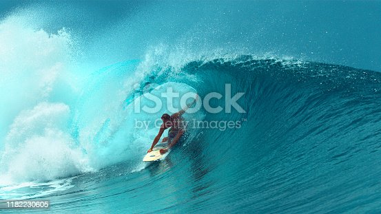 CLOSE UP: Young professional surfboarder finishes riding another epic tube wave on a sunny day in French Polynesia. Surfer having fun in the refreshing emerald water on a perfect day for surfing.