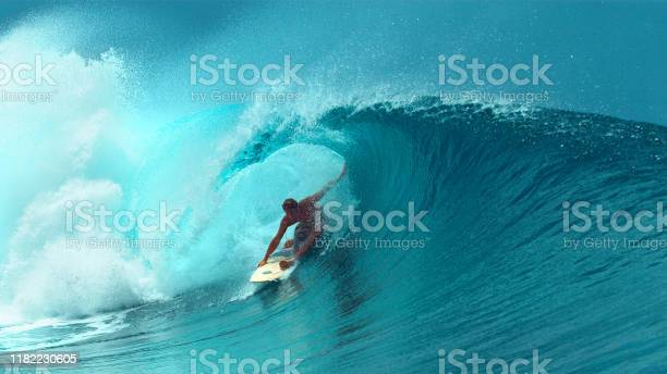 Photo of CLOSE UP: Professional surfboarder finishes riding another epic tube wave.