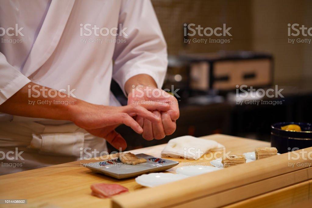 プロの寿司職人が慎重に右の圧力だけを使用して自信を持って完璧な寿司と献身にします。 ストックフォト
