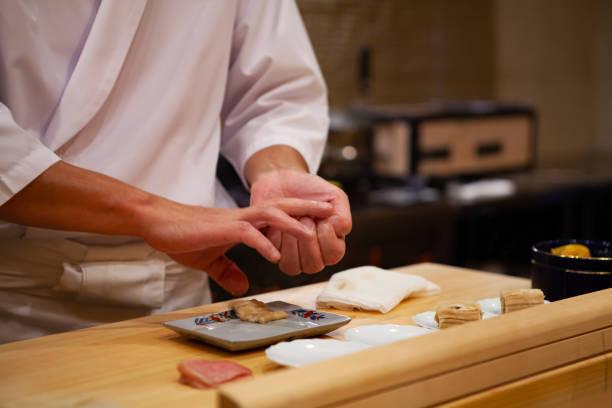 プロの寿司職人が慎重に右の圧力だけを使用して自信を持って完璧な寿司と献身にします。 - 日本食 ストックフォトと画像